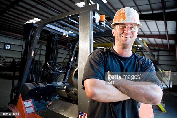 Male worker standing by forklift in warehouse