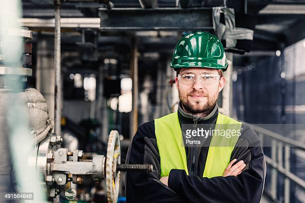 Male worker standing with arms crossed in factory