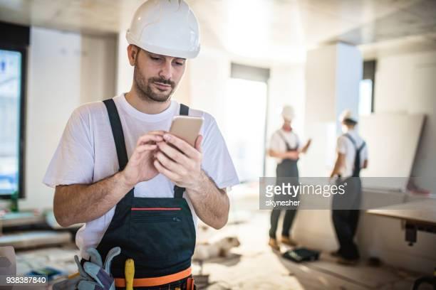 Männliche Arbeiter Textnachrichten auf Smartphone dabei bei der Renovierung nach Hause.