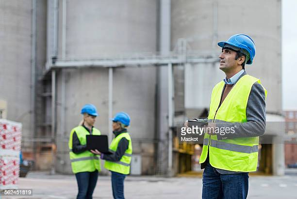 Male worker using digital tablet while looking away at factory
