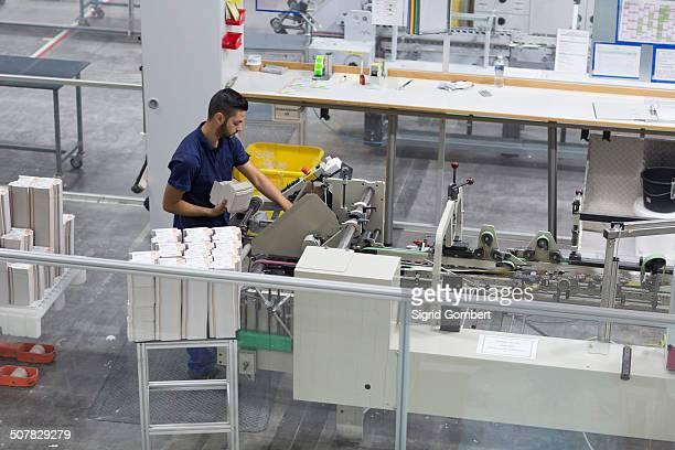 male worker using machine in paper packaging factory - sigrid gombert stock-fotos und bilder