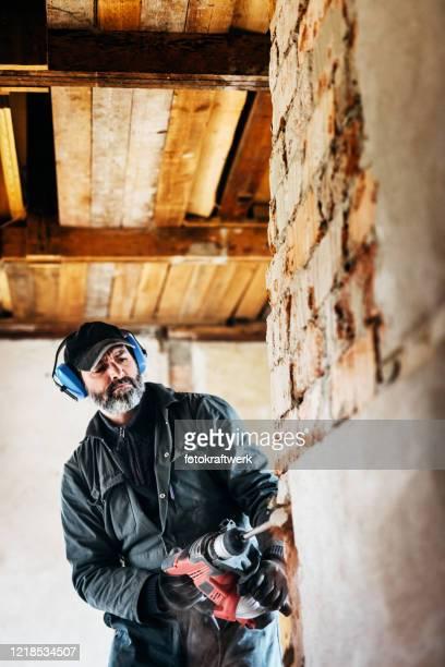 mannelijke arbeider die pneumatische hamerboor gebruikt om de steen van het muurconcrete snijden - herbouwen stockfoto's en -beelden