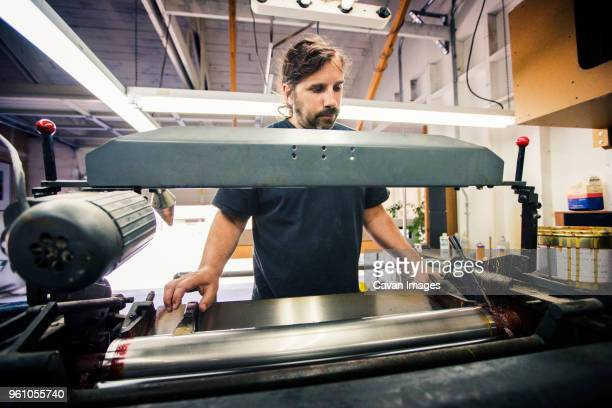 male worker using printing machine at workshop - printmaking technique stock pictures, royalty-free photos & images