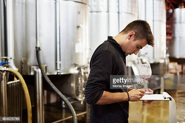Male worker writing remarks on wine in winery
