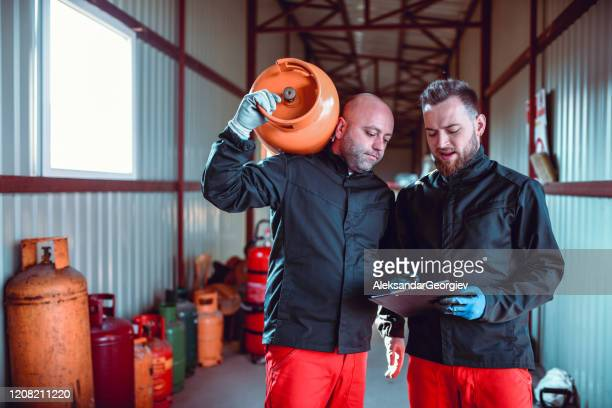 male workers in liquified gas store checking schedule - butane stock pictures, royalty-free photos & images