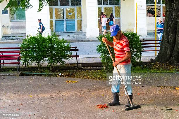 Male workers of the Communal Service Company or Empresa de Comunales cleaning the Leoncio Vidal Plaza Cuban lifestyle as the city wakes up