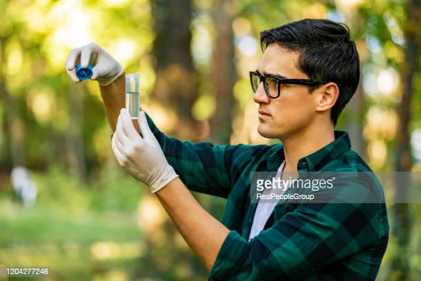 male working checking controlling the quality of water with glass tube.young ecologist man in the forest - ecologist stock pictures, royalty-free photos & images