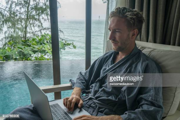 male working from private pool villa using laptop, travel concept - expatriate stock pictures, royalty-free photos & images