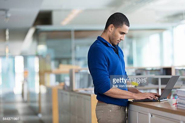 Male working on laptop at file cabinets