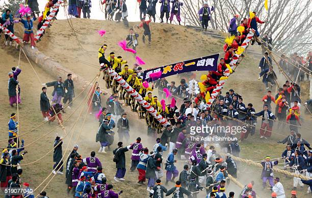 Male worshipers cling on the log careening down the hillside during the 'Kiotoshi' ritual as a part of Onbashira Festival on April 3 2016 in Chino...