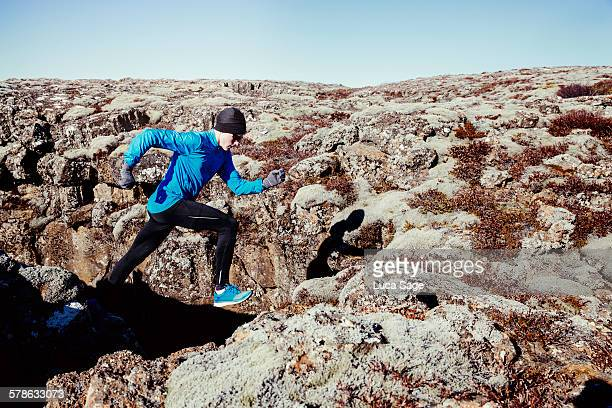 Male X-treme runner leaps in mossy rocky landscape