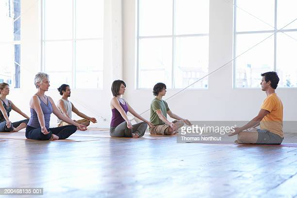 Male yoga instructor teaching class of five adults, side view