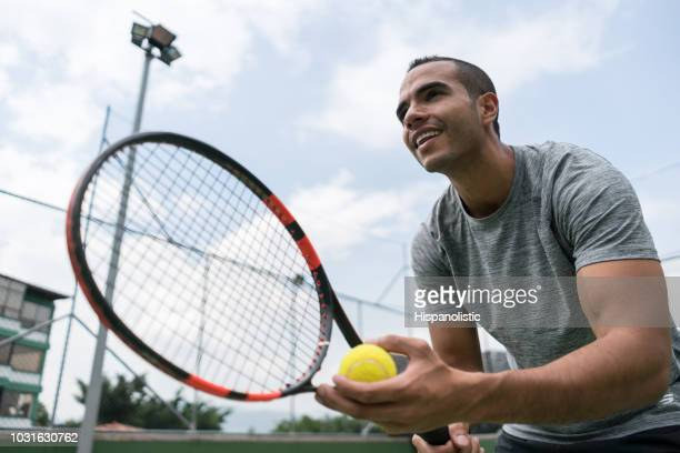 male young tennis player ready to start a game holding his racket and a tennis ball - tennis player stock pictures, royalty-free photos & images