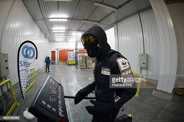Malek Boukerchi runs on a treadmill in a refrigerated storage unit in Montsoult north of Paris on November 7 to test equipment and train for the...