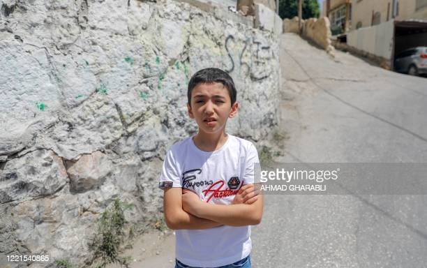 Malek Issa who lost his left eye, stands at the place where he was shot in Jerusalem on June 8, 2020. - Along the border of the Gaza Strip, the...