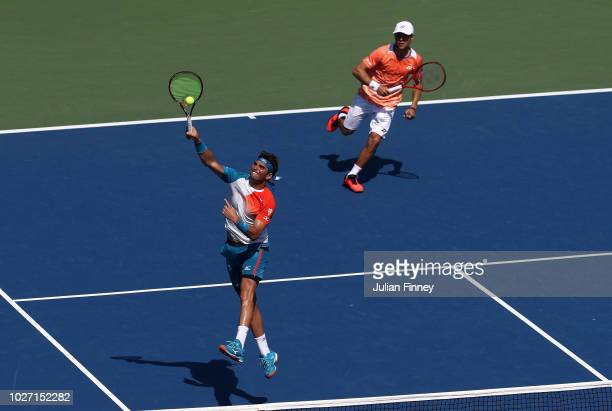 Malek Jaziri of Tunisia and Radu Albot of Moldova return the ball during their men's doubles quarterfinal match against Jamie Murray of Great Britain...