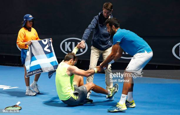Malek Jaziri of Tunisia is helped up by his oponent Salvatore Caruso of Italy after injuring himself during their match on day one of the 2018...