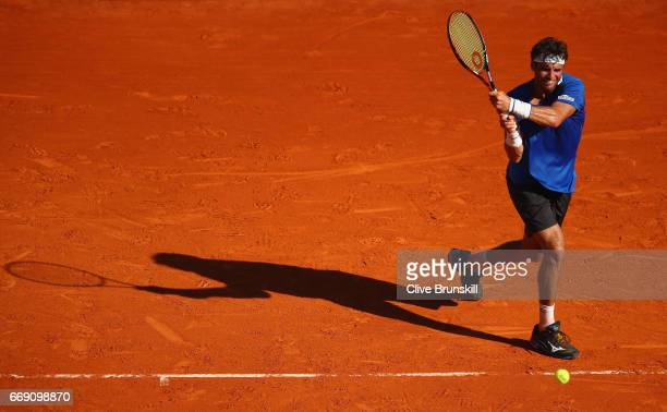 Malek Jaziri of Tunisia plays a backhand against Gilles Simon of France in their first round match on day one of the Monte Carlo Rolex Masters at...