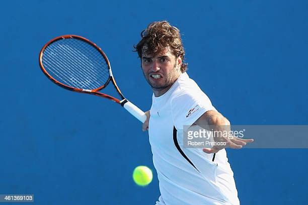 Malek Jaziri of Tunisia plays a forehand in his match against Austin Krajicek of United States during qualifying for the 2014 Australian Open at...