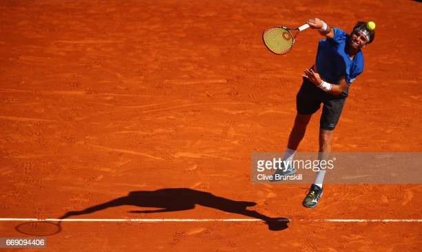 Malek Jaziri of Tunisia serves against Gilles Simon of France in their first round match on day one of the Monte Carlo Rolex Masters at MonteCarlo...