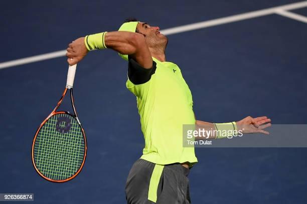 Malek Jaziri of Tunisia serves during his semi final match against Roberto Bautista Agut of Spain on day five of the ATP Dubai Duty Free Tennis...