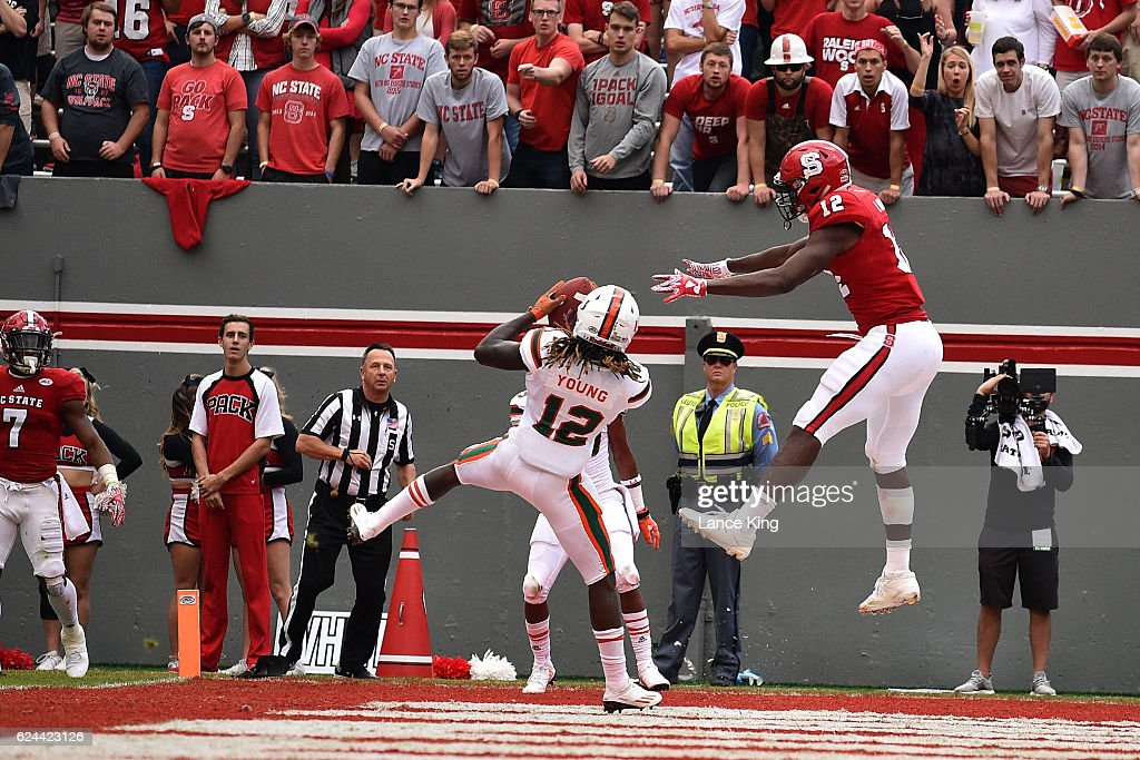Malek Young #12 of the Miami Hurricanes intercepts a pass intended for Bra'Lon Cherry #13 of the North Carolina State Wolfpack at Carter-Finley Stadium on November 19, 2016 in Raleigh, North Carolina. Miami won 27-13.