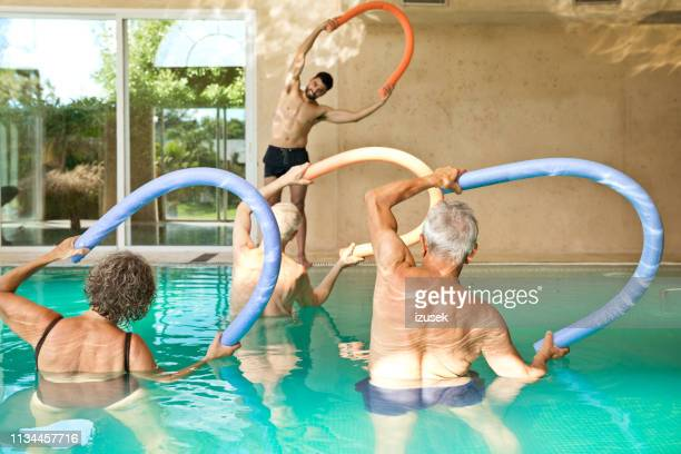 males and females exercising in swimming pool - retirement community stock pictures, royalty-free photos & images