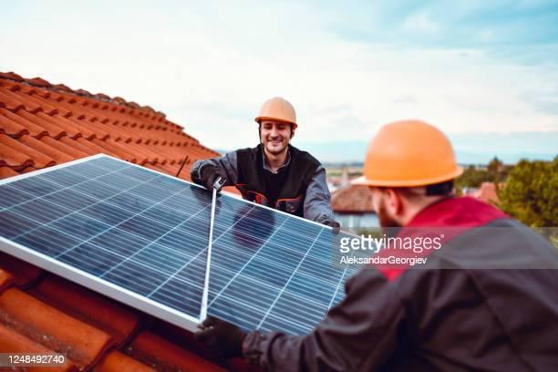 mâles vérifiant la largeur de panneau solaire - production d'énergie photos et images de collection