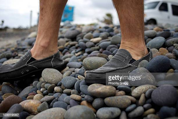 Male's feet walking on the rocks at the beach.