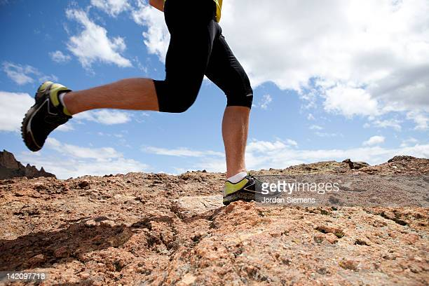 Male's legs trail running on rocks.