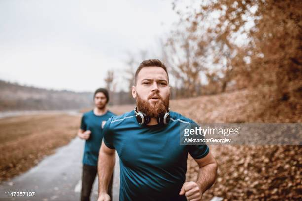 males running on track in golden autumn weather - all weather running track stock pictures, royalty-free photos & images