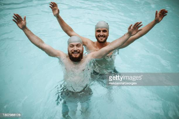 males stretching out arms and enjoying swimming pool freedom - competition group stock pictures, royalty-free photos & images