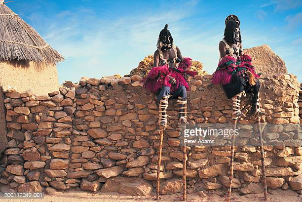 Mali, Dogon Country, two male stilt dancers sitting on stone wall