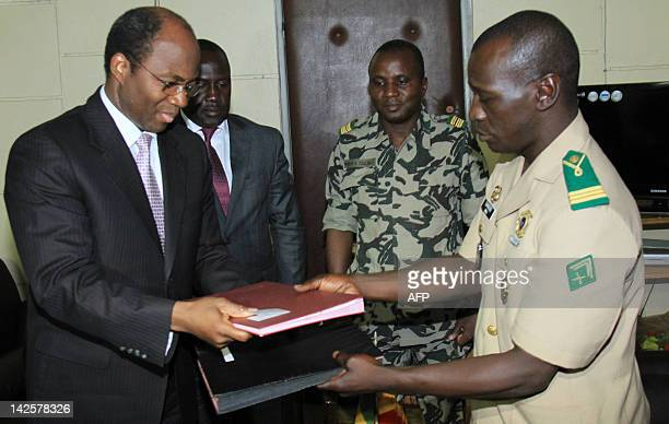 Mali junta leader Captain Amadou Sanogo exchanges documents with Burkina Faso's foreign Minister Djibrill Bassole next to Ivory Coast Minister of...