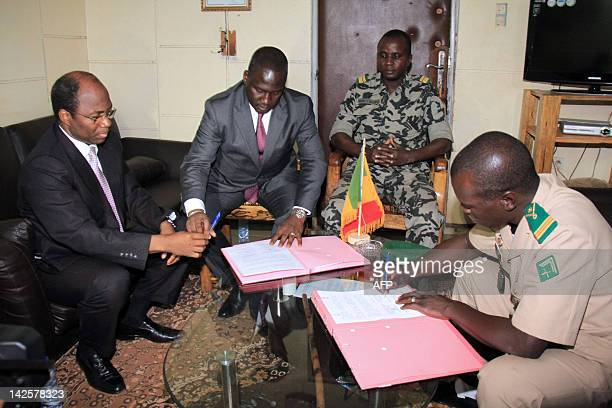 Mali junta leader Captain Amadou Sanogo signs documents next to Burkina Faso's foreign Minister Djibrill Bassole and Ivory Coast Minister of African...