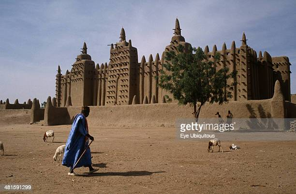 Mali Sahel Djenne Grand Mosque with man walking past and sheep in the foreground