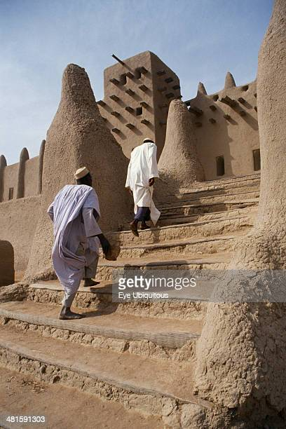 Mali Sahel Djenne Two men walking up steps leading to Grand Mosque