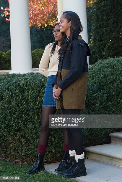 Malia and Sasha Obama daughters of US President Barack Obama look on as their father 'pardons' the National Thanksgiving Turkey in the Rose Garden at...