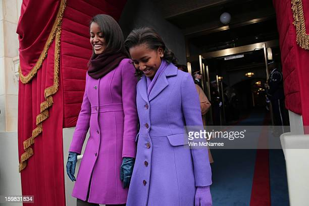 Malia Obama and Sasha Obama arrive during the presidential inauguration on the West Front of the US Capitol January 21 2013 in Washington DC Barack...