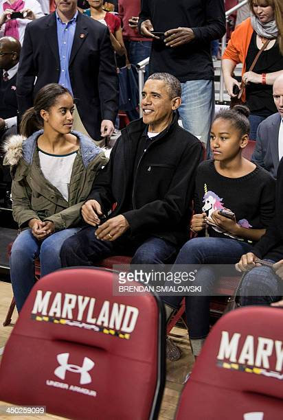 Malia Obama and Sasha Obama sit with their father US President Barack Obama during a basketball game at the University of Maryland's Comcast Center...