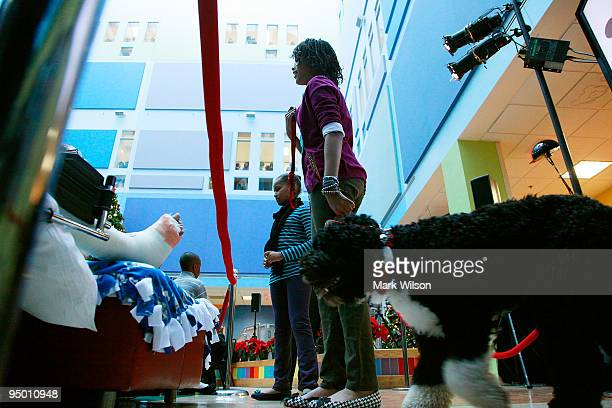 Malia Obama and Sasha Obama take their dog Bo around to visit patients while at the Children's National Medical Center with their mother first lady...