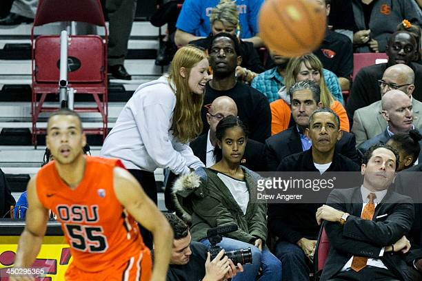 Malia Obama and U.S. President Barack Obama watch the action during a men's NCCA basketball game between University of Maryland and Oregon State...