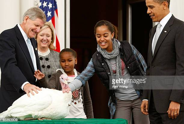 Malia Obama daughter of US President Barack Obama pats a turkey named 'Courage' as her sister Sasha and Walter Pelletier Chairman of the National...