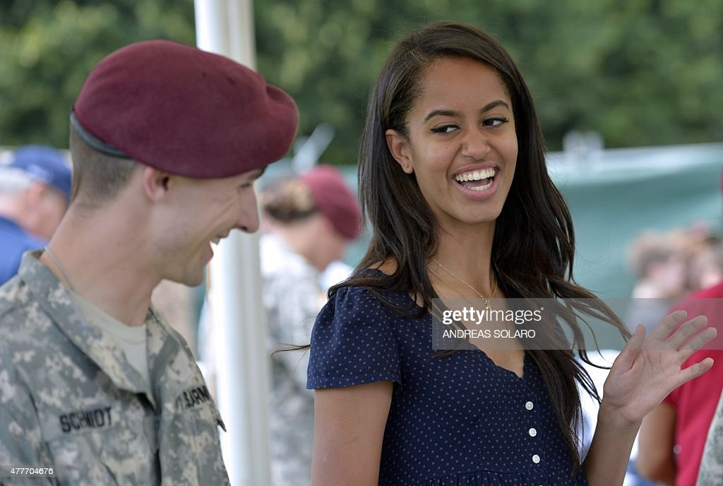 Malia Obama, daughter of US President, (R) smiles as she serves food during a lunch at the United States and Nato military base in Vicenza on June 19, 2015 .