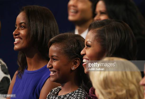 Malia Obama Sasha Obama and First lady Michelle Obama watch as Democratic presidential candidate US President Barack Obama speaks on stage during the...