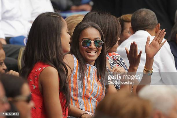 Malia Obama Sasha Obama US first lady Michelle Obama and President Barack Obama react to the first run scored during an exhibition game between the...