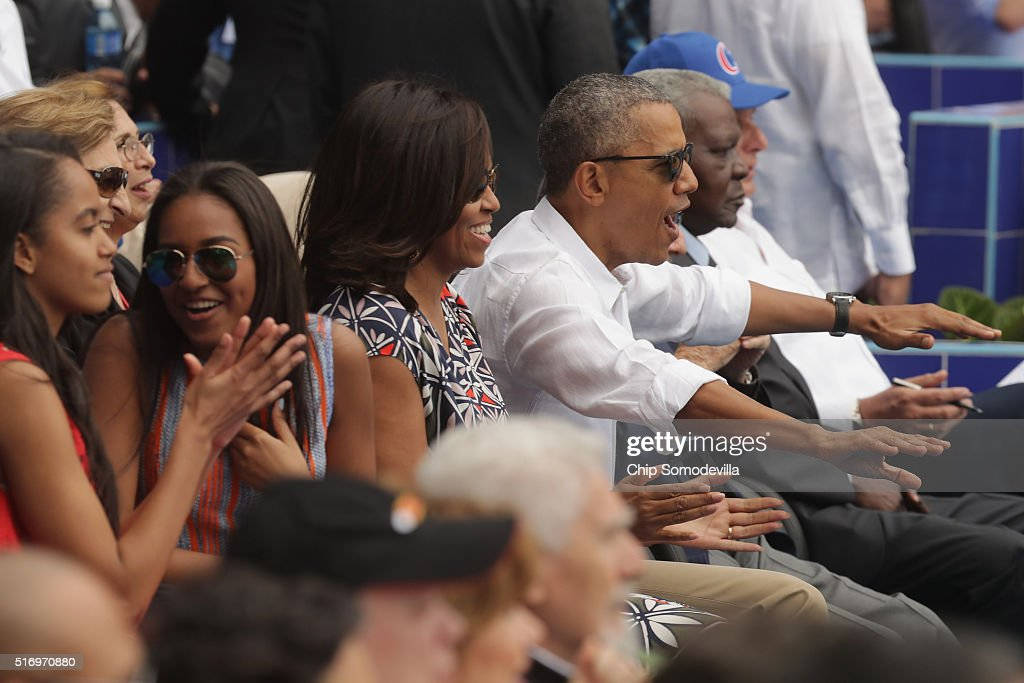 Malia Obama, Sasha Obama, U.S. first lady Michelle Obama, President Barack Obama and Cuban President Raul Castro react to the first run scored during an exhibition game between the Cuban national baseball team and Major League Baseball's Tampa Bay Devil Rays at the Estado Latinoamericano March 22, 2016 in Havana, Cuba. This is the first time a sittng president has visited Cuba in 88 years.