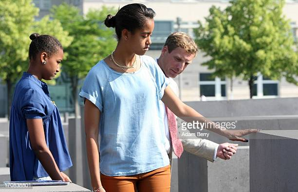 Malia Obama touches one of the stelae at the Memorial to the Murdered Jews of Europe next to her sister Sasha and Uwe Neumaerker director of the...