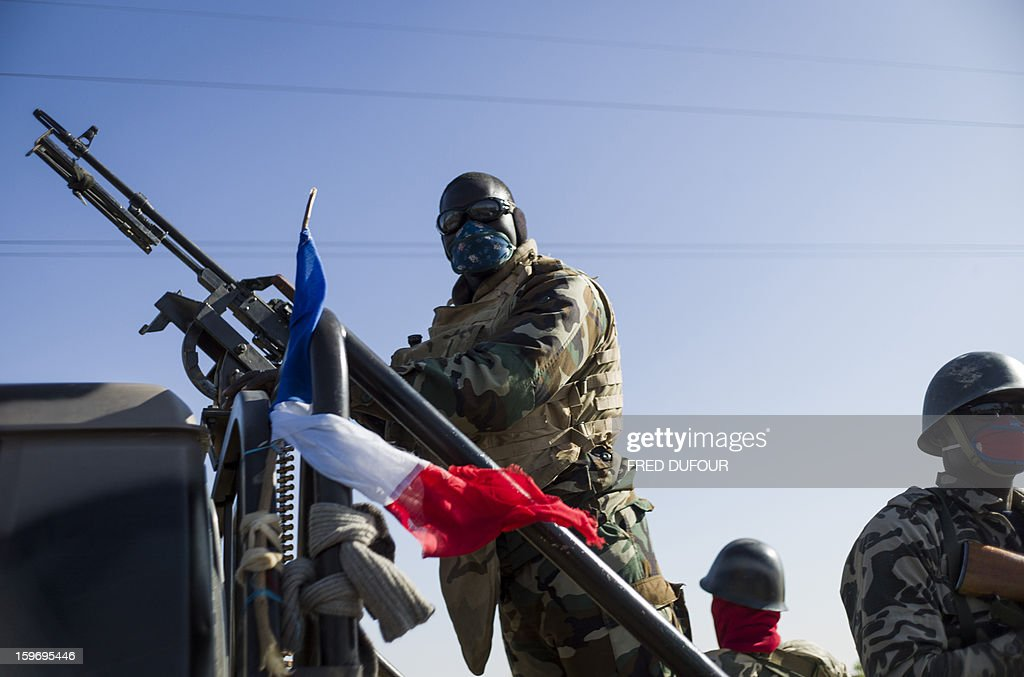A Malian army soldier holds a machine gun with a French flag wrapped on its side as he and others head towards Niono, on January 18, 2013. France now has 1,800 troops on the ground in Mali, inching closer to the goal of 2,500 it plans to deploy in its African former colony, Defence Minister Jean-Yves Le Drian said today. That was 400 more than a day earlier, said the minister as he met with French special forces in the western port of Lorient. The troops have been sent to help the Malian army regain control of the north from Islamist groups.