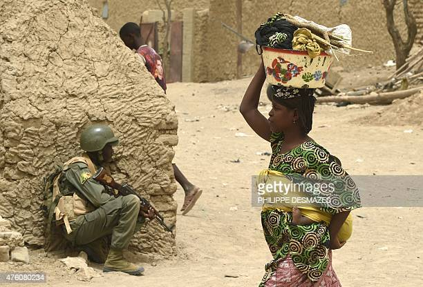 A Malian army soldier takes position after the arrest of two suspected looters in the village of Bintagoungou on June 4 near Goundam 80 km east of...